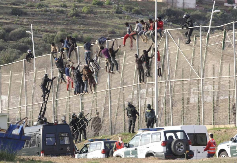 Inmigrantes y guardias civiles en la valla de Melilla