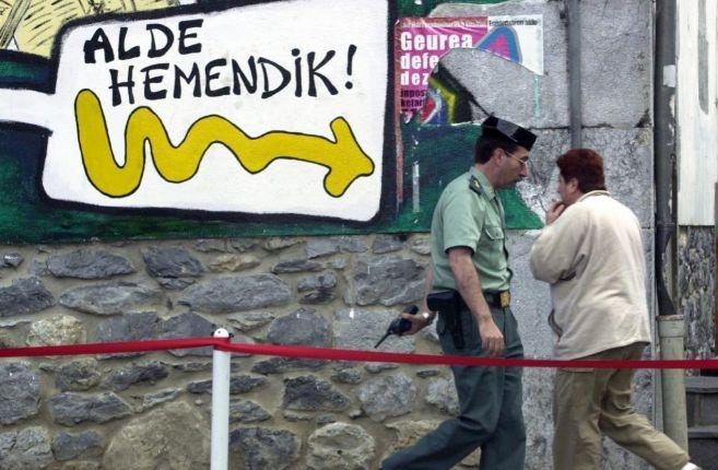 Un guardia civil pasa frente a una pintada en Oñate