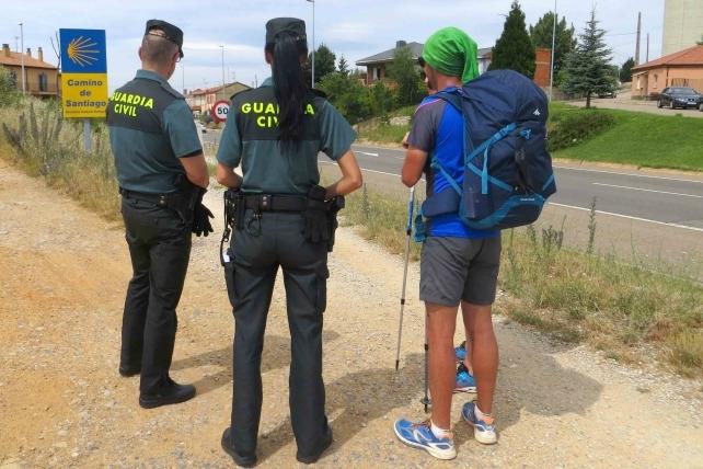 Dos guardias civiles atienden a un peregrino en el Camino de Santiago.