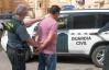 Un guardia civil conduce a un detenido al vehículo oficial..