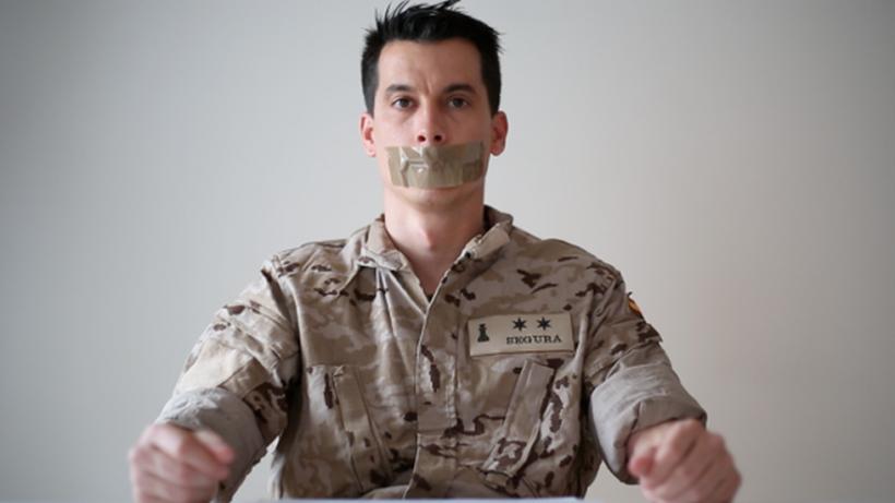 El Teniente Luis Gonzalo Segura, representando la mordaza que se le ha aplicado al expulsarlo del Ejército.