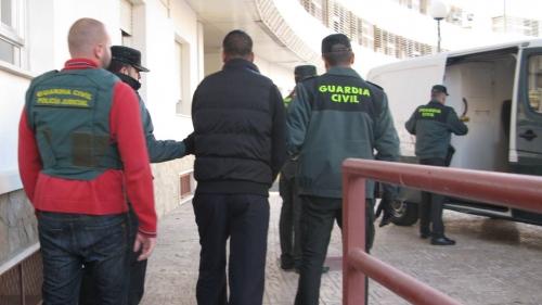 Un detenido es conducido hacia el furgón por parte de varios agentes.