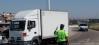 Un guardia civil regula el tráfico de un camión.