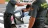 Un agente introduce a un detenido en un coche oficial.