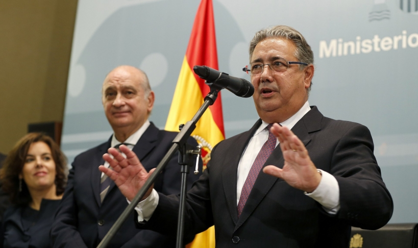 El ministro del Interior, Juan Ignacio Zoido, con su predecesor en el cargo, Jorge Fernández Díaz, ambos contemplados por una satisfecha Soraya Sáenz de Santamaría.