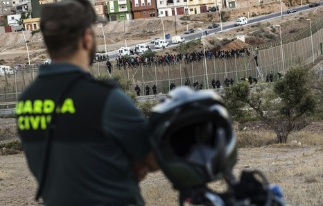 Un guardia civil vigila la frontera de Melilla, sobre cuya valla permanecen numerosos inmigrantes.