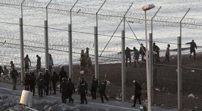 Guardias civiles e inmigrantes en la valla fronteriza del Tarajal, en Ceuta
