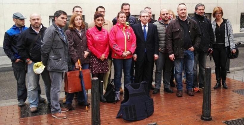 Las guardias civiles Pilar Villacorta y Alicia Sánchez, ambas de rojo, posan a las puertas del tribunal militar de Valladolid con representantes de AUGC frente a un chaleco antibalas.