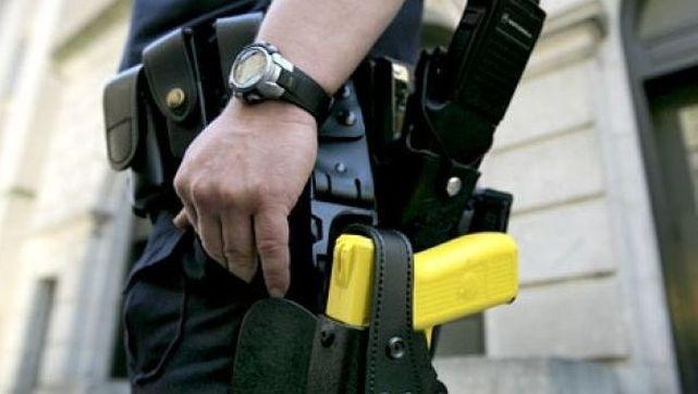 Un policía británico, equipado con un arma eléctrica.