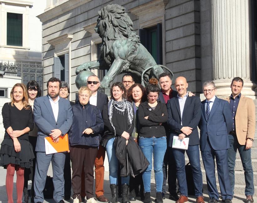 Representantes de distintos grupos parlamentarios y de AUGC posan frente al Congreso con Alicia Sánchez (en el centro, con pañuelo).