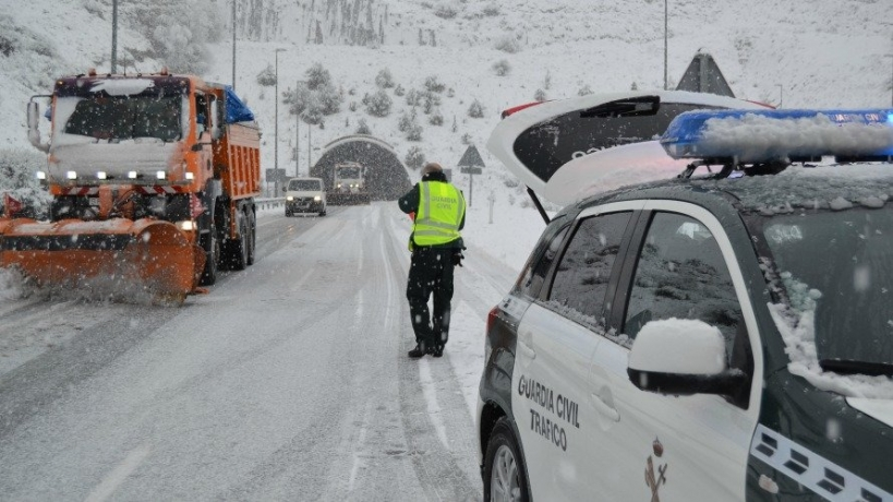 Un guardia civil atiende el tráfico en medio de una nevada.