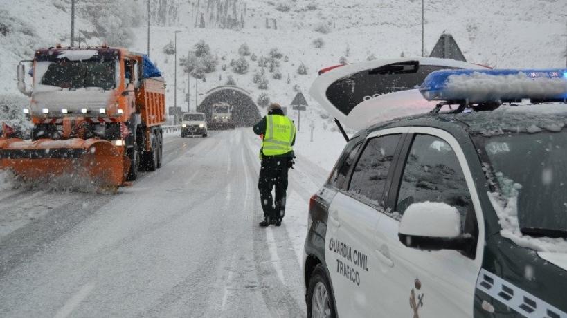 Un guardia civil atiende el tráfico en medio de una nevada.