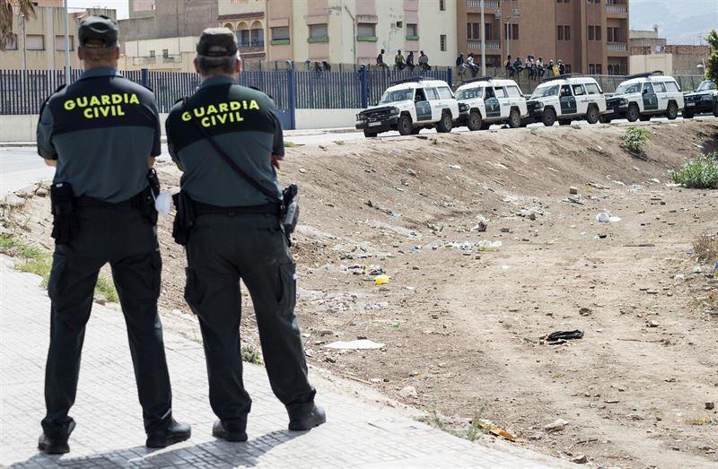 Dos guardias civiles vigilan una valla fronteriza.