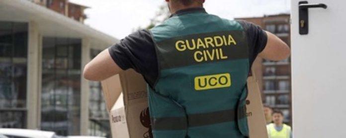 Un agente de la UCO carga una caja con documentación realacionada con una investigación.