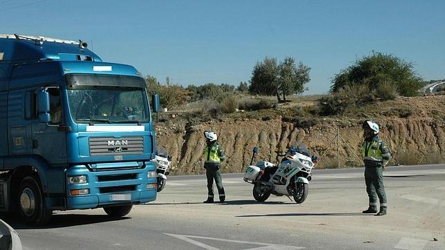 Dos agentes de Tráfico proceden al desvío de un camión