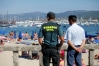 Un guardia civil y un agente local vigilan una playa.