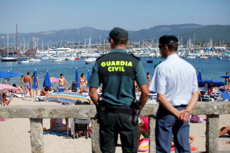 Un guardia civil y un agente local vigilan una playa.