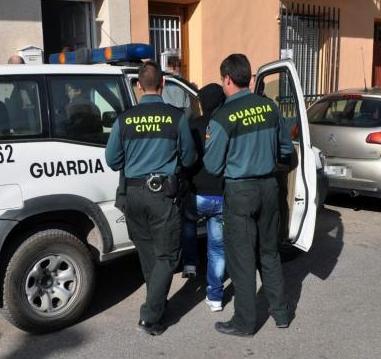 Dos guardias civiles introducen a un detenido en un vehículo oficial