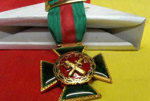 Cruz de la Orden del Mérito de la Guardia Civil con distintivo rojo.