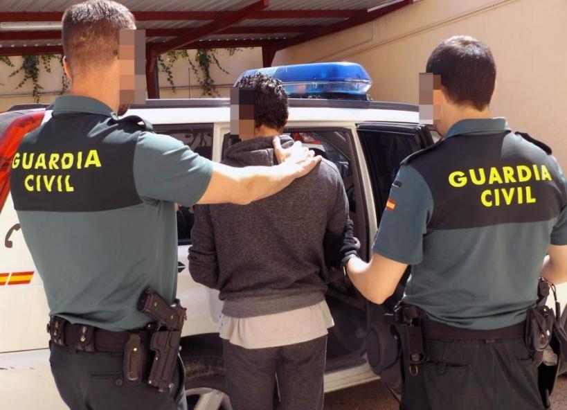 Dos guardias civiles conducen a un detenido.