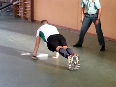 Un agente realiza flexiones ante un evaluador.