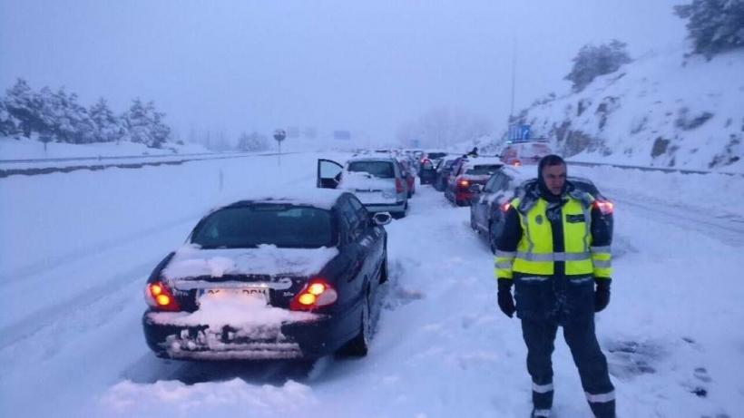 Un guardia civil junto a vehículos atrapados por el temporal en la AP6.