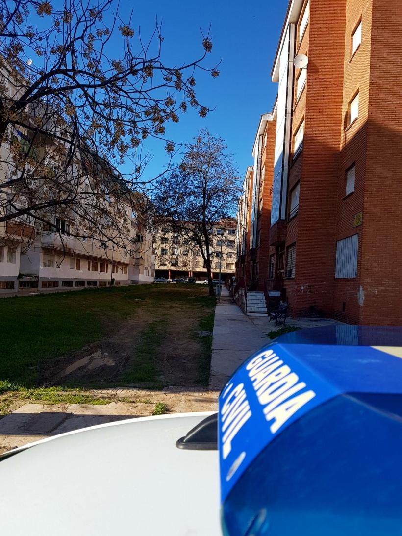 Un vehículo oficial presta vigilancia al bloque de viviendas de la Guardia Civil que había sido 'okupado' en una barriada de Badajoz.