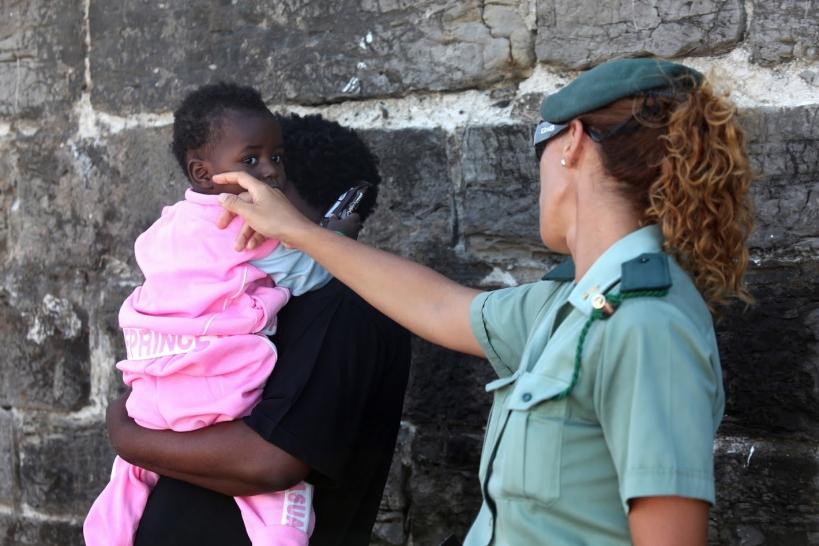 Una guardia civil atiende a una madre inmigrante y a su hija.