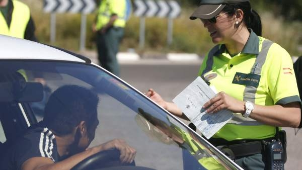 Una guardia civil de Tráfico solicita su documentación a un conductor.