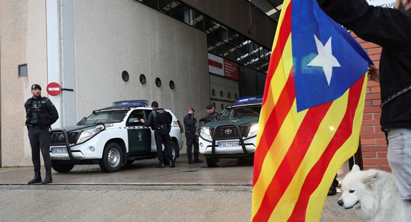 Un independentista exhibe una estelada ante guardias civiles en Cataluña.