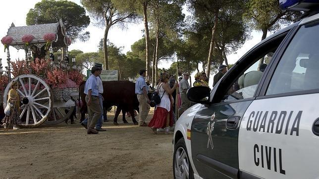 Un vehículo de la Guardia Civil ante participantes en la romería de El Rocío.