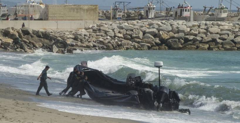 Guardias civiles empujan una lancha semirrígida utilizada por los narcos en el Estrecho. Foto: El País