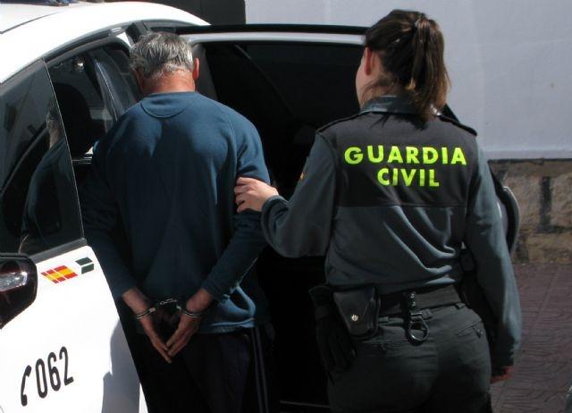 Una guardia civil conduce a un detenido al interior de un vehículo oficial.
