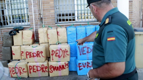 Un guardia civil señala fardos de droga incautados en Campo de Gibraltar. Foto: EFE