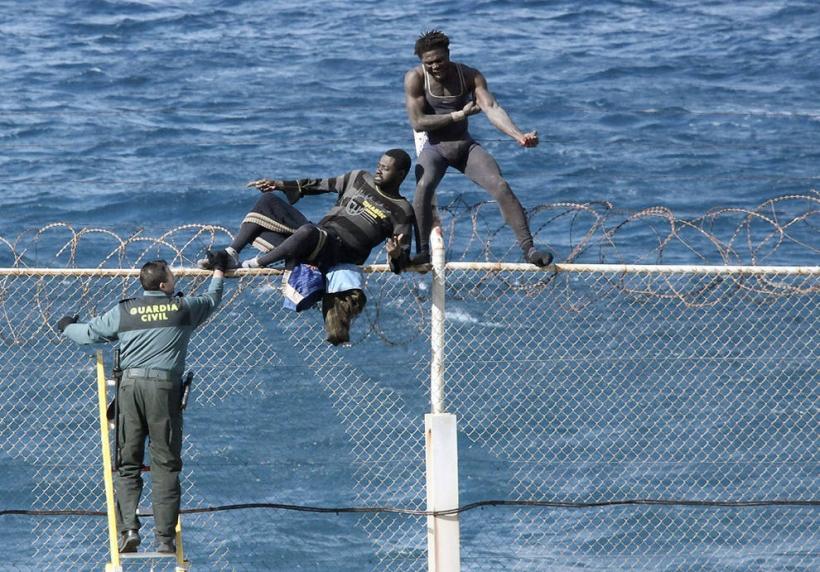 Un guardia civil trata de repeler un asalto de inmigrantes a la valla de Ceuta. Foto: EFE