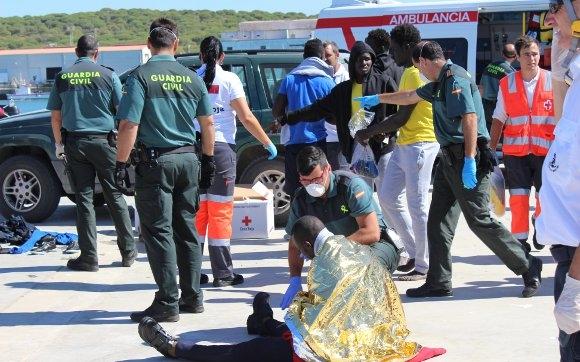 Guardias civiles atienden a inmigrantes recién llegados a la costa.