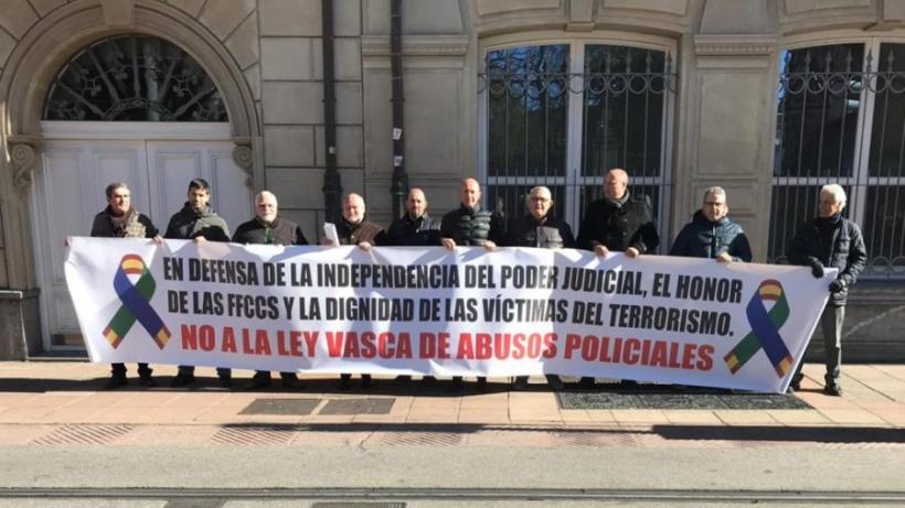 Representantes de AUGC y otras organizaciones policiales muestran su pancarca contra la ley vasca aprobada hoy.
