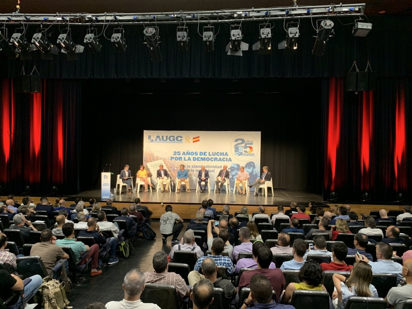 Vista panorámica del salón de actos en el que se celebró el evento. Al fondo, el escenario y los participantes en el debate.
