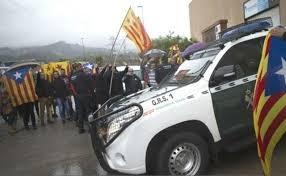 Un vehículo de la Guardia Civil ante un grupo de independentistas.