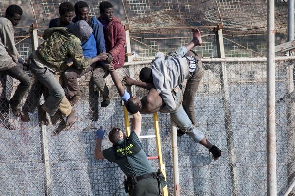 Un guardia civil se enfrenta a un intento de saltar la valla por parte de un grupo de inmigrantes subsaharianos.