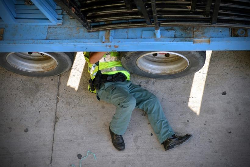 Un guardia civil examina los bajos de un vehículo.